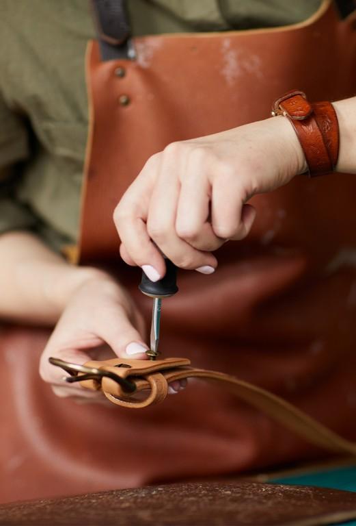 Käsityöläinen korjaa nahkavyötä