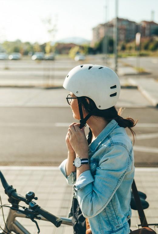 Pyöräilijä laittaa kypärää